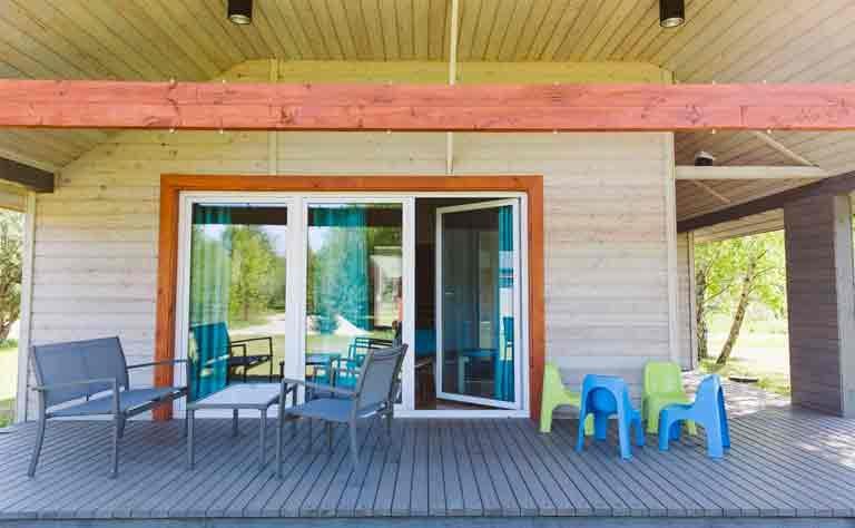 Sitzgelegenheit fuer Gross und Klein auf der geraeumigen Terrasse vom Bungalow am See in Polen
