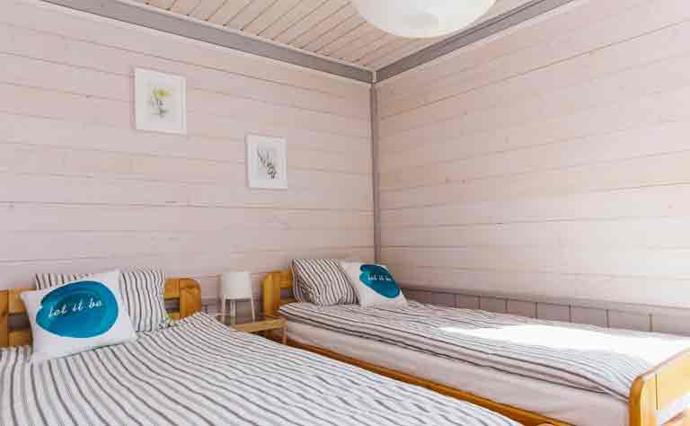lichtes Schlafzimmer mit zwei Einzelbetten in den Habenda-Houses - Bettwaesche ist vor Ort
