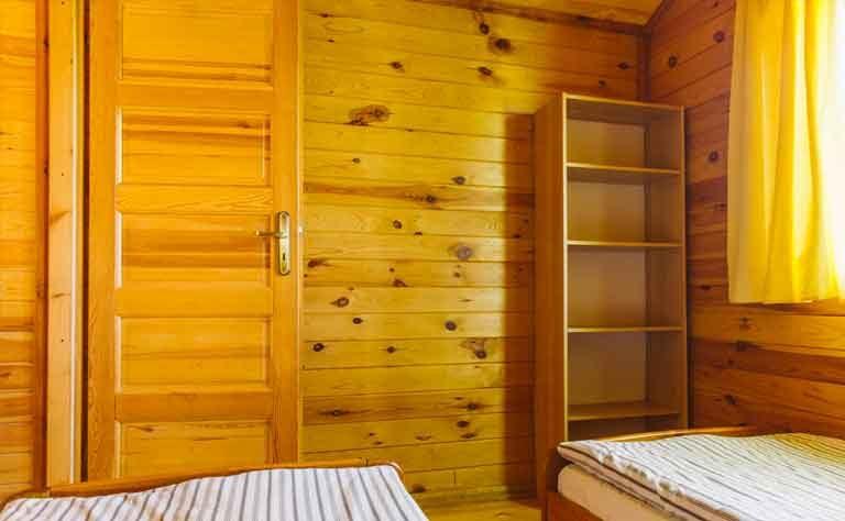 Schlafzimmer mit zwei Einzelbetten und Regalschrank im Ferienhaus am See in Polen