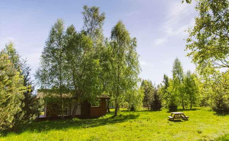 Holzhaus mit Sitzgelegenheit auf der Wiese fuer den Urlaub an der Ostsee in Polen